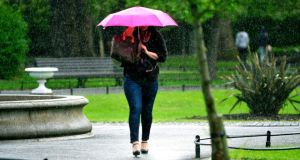 A woman walks through a rain shower on May 31st in  Saint Stephen's Green in Dublin. Photograph: Aidan Crawley/The Irish Times