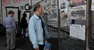 Members of the public read newspaper reports about the growing Greek debt crisis in Athens. Photograph: Orestis Panagiotou/EPA