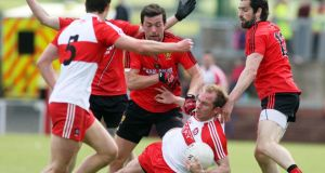 Derry's Sean Leo McGoldrick and Down's Damien Turley tussle for the ball. Photo: Lorcan Doherty/INPHO