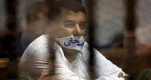 "Journalist Ibrahim Aladrawi looks on behind bars with a sign reading ""Journalist"" taped over his mouth during his court appearance with Muslim Brotherhood members on the outskirts of Cairo, earlier this month. Photograph: Amr Abdallah Dalsh/Reuters"