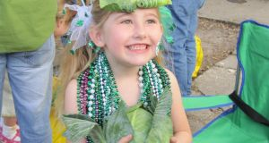 In New Orleans parades are interactive affairs and among other items riders on the floats throw to spectators everything you need to make an Irish stew except the meat – cabbage, potatoes, carrots, onions, and garlic! Here Reily Brown just caught a cabbage and promptly placed a leaf on her head as a hat!