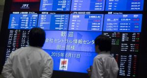 Men look at a display showing market indices at the Tokyo Stock Exchange (TSE) in Tokyo . Photograph: Thomas Peter/REUTERS