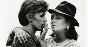Detail from a photograph by Terry O'Neill of David Bowie and Elizabeth Taylor sharing a cigarette during their first meeting in Beverly Hills in 1975