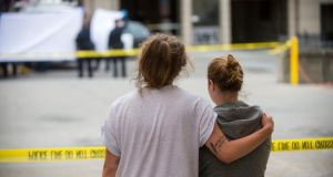 Two women embrace while watching sheriff's deputies on duty at the scene in Berkeley where six Irish students were killed. They said hthey knew the victims. Photograph: AP Photo/Noah Berger