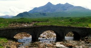 Looking across a bridge towards the rocky ridge of the Cuillin mountains from Sligachan, the Isle of Skye. Photograph: Paul Tomkins/Visit Scotland