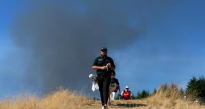 Ireland's Shane Lowry walks the 15th hole as smoke from a nearby fire is seen in the distance during the third round of the  US Open  at Chambers Bay  in University Place, Washington. Photo: Andrew Redington/Getty Images