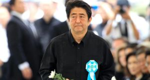 Japan's prime minister Shinzo Abe walks towards a memorial to lay flowers for victims of the second World War Battle of Okinawa during a memorial service on Tuesday. Photograph: Hitoshi Maeshiro/EPA