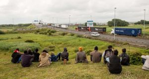 Migrants sit near the A16 highway as they try to access the Channel Tunnel on in Calais, northern France. Photograph: Philippe Huguen/AFP/Getty Images