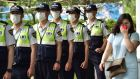 A woman walks past South Korean policemen wearing face masks in Seoul, South Korea. Photograph: Getty