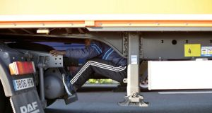 A migrant sits under the trailer of a lorry as he attempts to cross the English Channel in Calais, northern France on Wednesday. Photograph: Thibault Camus/AP.