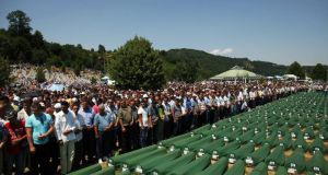 Bosnia Muslims pray near coffins at the memorial centre in Potocari during a mass burial near Srebrenica three years ago. Photograph: Dado Ruvic/Reuters