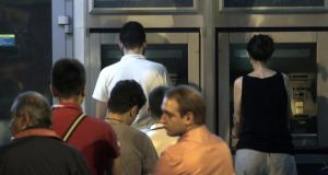 People wait in a queue to withdraw money from the ATM outside a branch of Greece's National Bank in Athens, on Saturday. Photograph: EPA