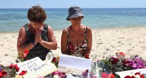 Tourists pray beside flowers placed in tribute to the people killed in a terror attack on a beach in front of the imperial Marhaba Hotel in Sousse,Tunisia, on Sunday. Photograph: EPA