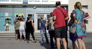 People line up to withdraw cash on the Greek island of Crete on Sunday. Photograph: Stefanos Rapanis/Reuters.