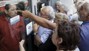 Pensioners waiting outside a closed National Bank branch and hoping to get their pensions, argue with a bank employee in Iraklio in Crete. Photograph: Stefanos Rapanis/Reuters