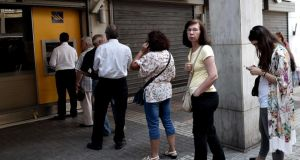People queue to withdraw cash from an ATM n central Athens on Tuesday. Photograph: Getty