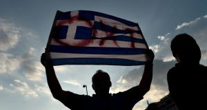 A protester waves a Greek flag during an anti-austerity rally in Athens, Greece. Photograph: Yannis Behrakis/Reuters