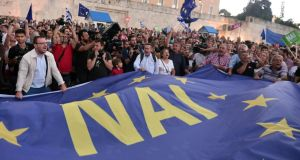 "Pro-Euro protesters hold a large European flag reading ""Yes"" in front of the parliament building in Athens on Tuesday evening. Photograph: Getty"