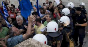 Pro-euro protesters tussle with riot police at a rally in front of the Greek parliament building in  Athens on Tuesday night. Photograph: Marko Djurica/Reuters