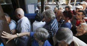 Pensioners struggle to enter an Alpha Bank branch in Athens on Wednesday.  Photograph: Reuters