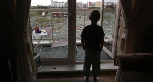 A child at his apartment window in the unfinished estate of Belmayne, Dublin, in 2011. File photograph:  Fran Veale