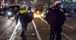 Riot police patrol in the Schilderswijk district of The Hague during the third night of riots following the death of a tourist in police custody. Photograph: Marco de Swart/AFP/Getty Images