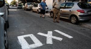 "Pedestrians walk along a road displaying an ""OXI"" or ""No"" campaign sign against bailout proposals in Athens, Greece, on Friday. Greece is divided  heading into Sunday's referendum on European bailout proposals. Photograph: Yorgos Karahalis/Bloomberg"