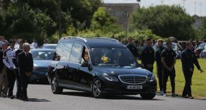The coffin of mother-of-two Lorna Carty, a victim of the Tunisia terror attack is carried in a hearse, escorted by players from Meath GAA and Dunderry GAA. Photograph: PA