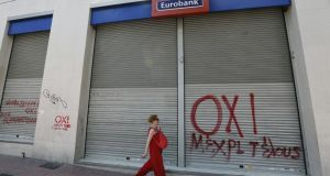 A woman walks by a closed Eurobank branch spray-painted with a NO graffiti in Athens. Photograph: Yannis Behrakis/Reuters