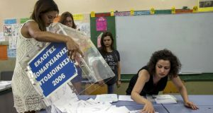 A ballot box is emptied by a voting official at the closing of polling stations in Athens, Greece. Photograph: Marko Djurica/Reuters