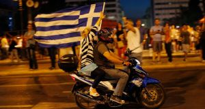 A supporter of the No vote waves a Greek flag after the first results of the referendum at Syntagma square in Athens. Photograph: AP Photo/Emilio Morenatti