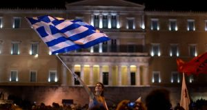 A supporter of the No vote waves a Greek flag in front of the parliament after the results of the referendum at Syntagma square in Athens. Photograph: Emilio Morenatti/AP Photo