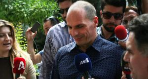 Journalists follow outgoing Greek finance minister Yanis Varoufakis as he leaves his home in Athens on Monday. Photograph: EPA.