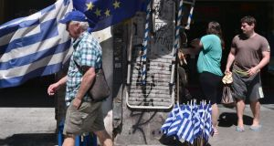 People walk past Greek and European Union flags on sale in Athens today. Photograph: Louisa Goulimaki/AFP/Getty