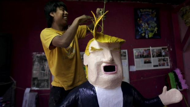 A worker hangs a paper mache figure depicting Republican presidential candidate Donald Trump at a workshop in Reynosa, Mexico, Angry Mexicans can beat it with a stick. Photograph: Reuters/Daniel Becerril