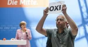 A protester holds a sheet with the Greek word for 'No' during an open house presentation of Germany's conservative Christian Democratic Union (CDU) party  in Berlin, while German chancellor Angela Merkel speaks in the background. Photograph: Getty Images