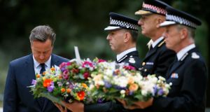 Britain's prime minister David Cameron bows as he stands with police officers after laying a wreath at the memorial to victims of the July 7th, 2005 London bombings, in Hyde Park, central London, Britain July 7th, 2015. Photograph: REUTERS/Peter Nicholls