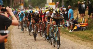 The peloton hits the cobbles on stage four of the Tour, a 223km stage between Seraing and Cambrai. Photograph: Bryn Lennon/Getty Images