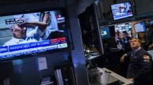 A trader works on the floor of the New York Stock Exchange look on as as news related to the falling stock market in China is shown on a television screen. Photograph: Reuters