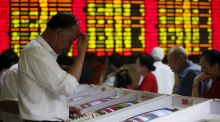 Investors look at computer screens showing stock information at a brokerage house in Shanghai. Photograph: Reuters/Aly Song