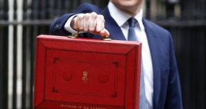 Welfare cuts contained in the new budget of British chancellor of the exchequer George Osborne (above, holding budget case), which will reduce payments to large families, will disproportionately hit poor  Catholics, a British Labour MP has claimed. Photograph: Simon Dawson/Bloomberg