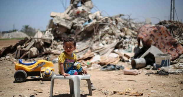 A Palestinian child sits in front of the rubble of buildings which were destroyed in the summer of 2014 in the southern Gaza Strip.