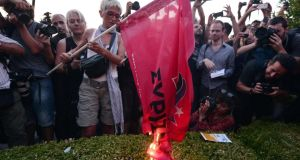 A woman burns the flag of the ruling party Syriza, while surrounded by journalists, in front of the Greek parliament in Athens during an anti-EU demonstration in Athens on Monday. Photograph: Louise Gouliamak/AFP/Getty
