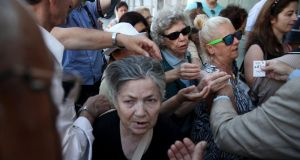 Pensioners are given priority tickets  as they wait to receive part of their pensions in Athens, Greece yesterday. REUTERS/Yiannis Kourtoglou