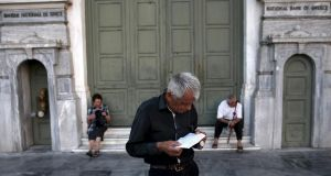 A pensioner waits to receive part of his pension at a National Bank branch in Athens. Euro zone leaders clinched a deal with Greece on Monday to negotiate a third bailout to keep the near-bankrupt country in the euro zone after a whole night of haggling at an emergency summit. Photograph: Yiannis Kourtoglou/Reuters