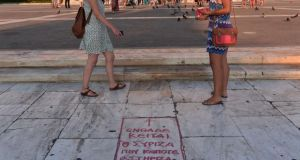 Women stand by a slogan written on the pavement reading 'Here lies Syriza, the party I once supported ' in front of the Greek parliament in Athens. Photograph: Louisa Gouliamaki/AFP/Getty Images