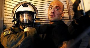 A protester  is arrested by riot police following clashes in Athens on Wednesday. Photograph: Yannis Behrakis/Reuters