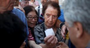 Pensioners are given priority tickets by a bank branch manager as they wait to receive part of their pensions in Athens on Thursday. Photograph: Reuters