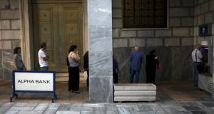 People line up at an ATM outside an Alpha Bank branch in Athens, Greece on July 16th, 2015. Greece awoke with a political hangover on Thursday after parliament approved a stringent bailout programme, thanks to the votes of the pro-European opposition, amid the worst protest violence this year. Photograph: Yiannis Kourtoglou/Reuters