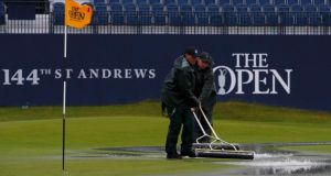 Groundstaff remove water from the first green after torrential rain forced play to be suspended during the second round of the British Open golf championship on the Old Course in St. Andrews. Photograph: Paul Childs/Reuters
